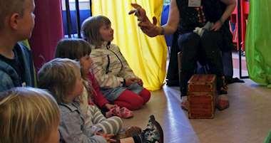Barn sitter och lyssnar på sagoberätterska med kasperdocka på handen.
