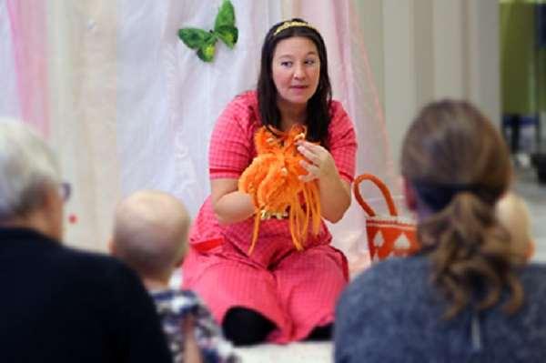 Kvinna i rosa klänning har en teater för små barn. Hon håller upp en stickad bläckfisk.