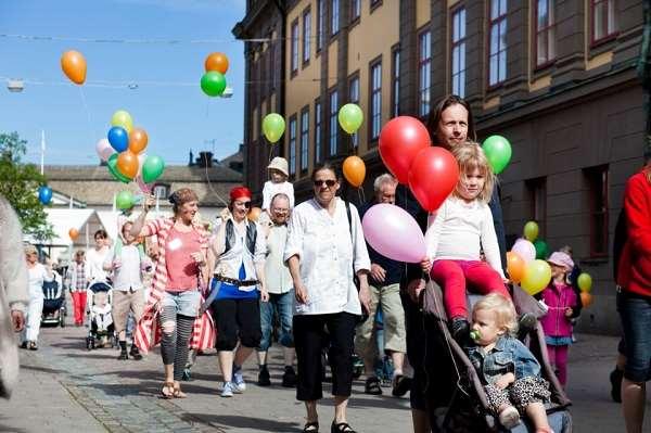 Parad med barn och vuxna går på en gata i en stad. Barnen har färgglada ballonger.