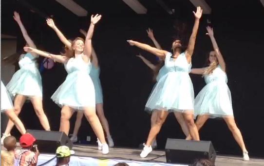 Tonårsflickor i ljusblå klänningar dansar på en scen.