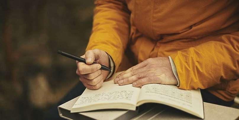Två händer vilar på uppslagen bok. Högerhanden håller i en penna.