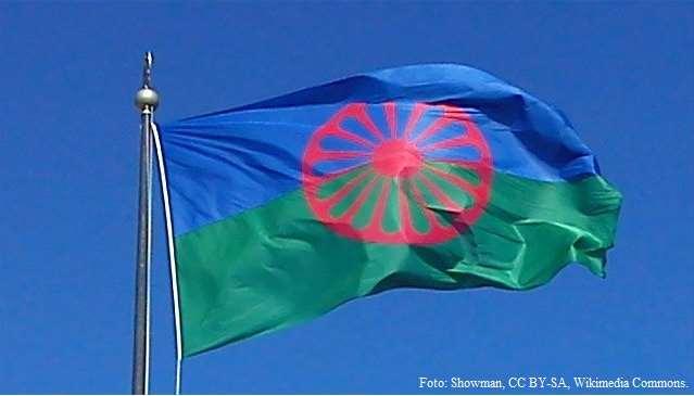 Den romska flaggan vajar i vinden mot en klarblå himmel.