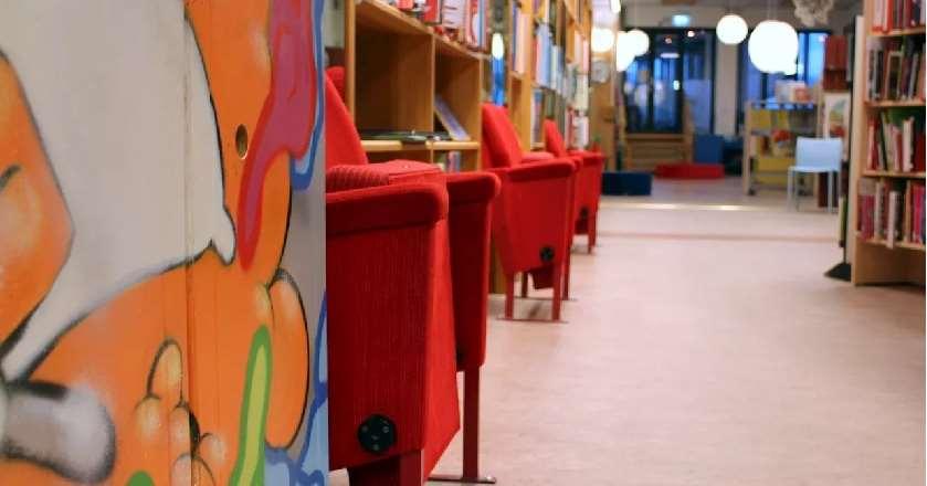Interiör från en hyllvägg och röda biofåtöljer på barn och ungdomsavdelningen.